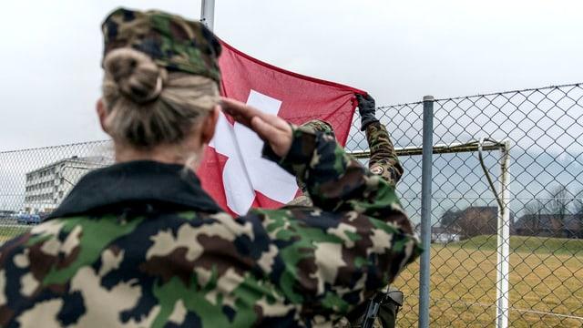 Eine Frau salutiert vor einer Schweizer Flagge
