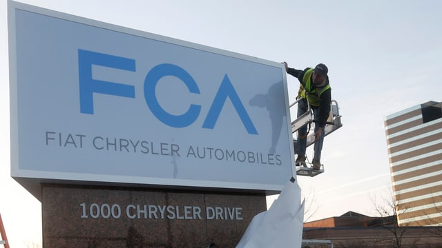 Arbeiter an Firmenschild von Fiat Chrysler