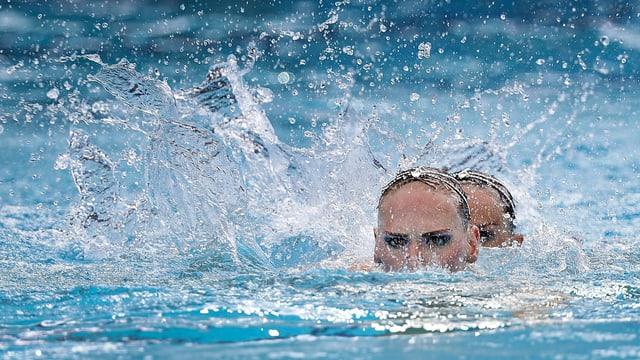 Schwimmerinnen halb unter Wasser.