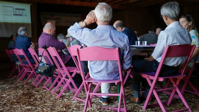 Mehrere Delegierte sitzen auf Stühlen in einem Bauernhof.