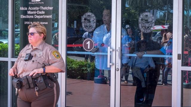 ina policista americana stat avant il local d'elecziun