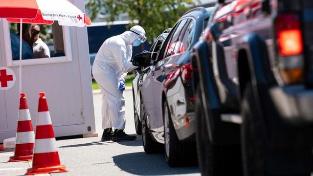 Eine Teststation: Autos stehen in einer Schlange, eine Person in Schutzanzug nähert sich einem Autofenster.