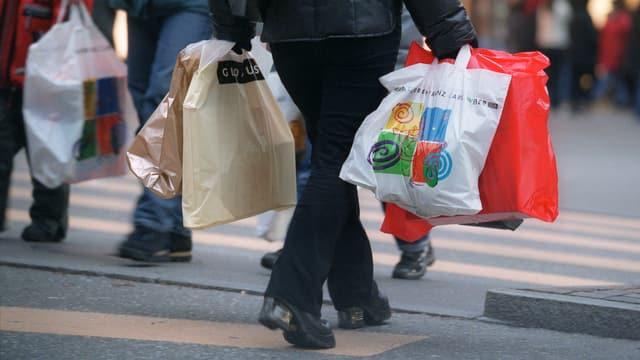 Eine Person mit Einkaufstaschen überquert einen Fussgängerstreifen.
