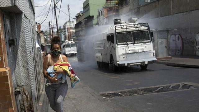 Frau mit Baby und Mundschutz