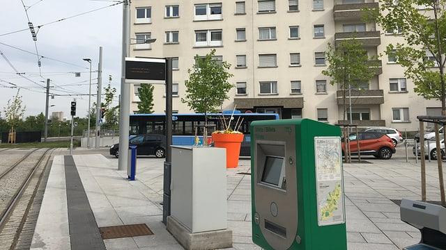 Eine Tramhaltestelle mit Billettautomat, im Hintergrund ein blauer Bus