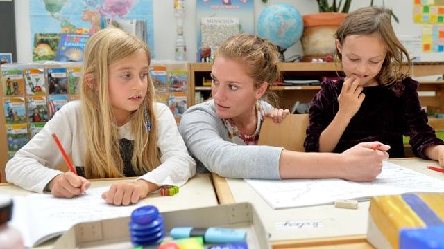 Eine Lehrerin erklärt zwei Schülerinnen etwas am Pult.