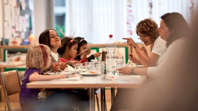 Kinder an einem Mittagstisch.