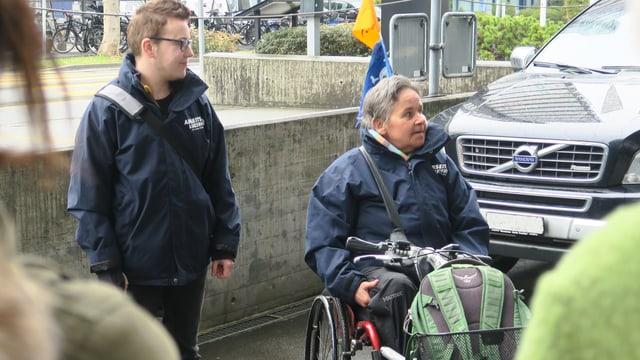 Ein junger Mann mit einer Umhängetasche auf der linken Bildseite, eine ältere Frau im Rollstuhl auf der rechten Bildseite vor einem Auto.