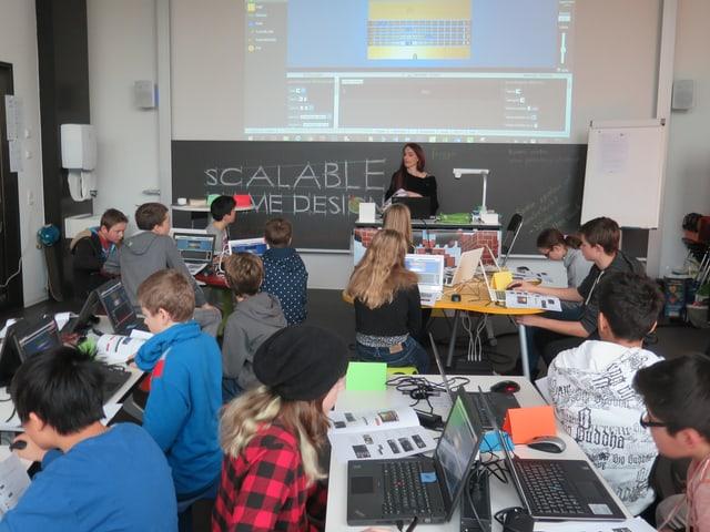 Ein Raum voller Kinder an Laptops