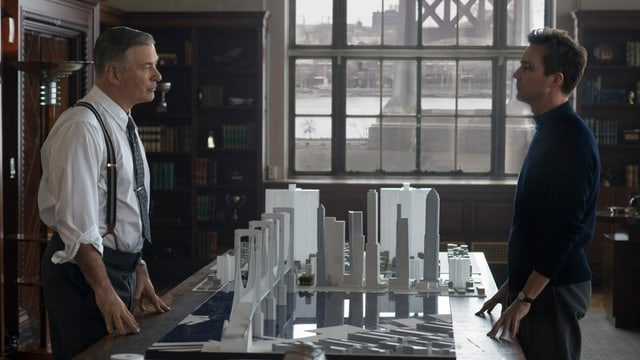 Zwei Männer stehen an einem Tisch mit Architekturmodellen.