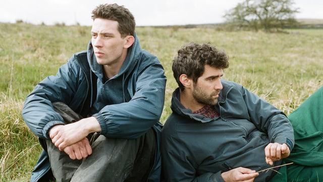 Zwei junge Hirten sitzen Rücken an Rücken in einer Wiese.