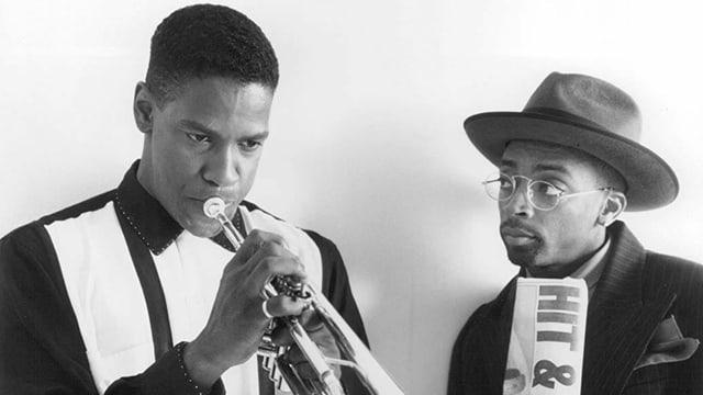 Denzel Washington spielt Trompete. Spike Lee schaut ihm dabei zu.