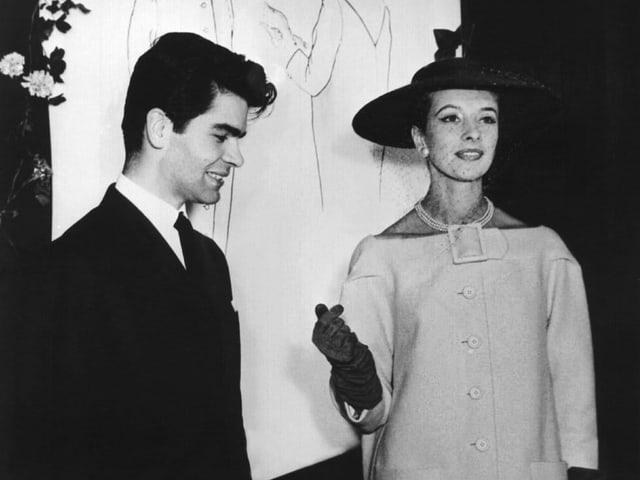 Der junge Karl Lagerfeld führt 1954 ein Model im Cocktailmantel vor.