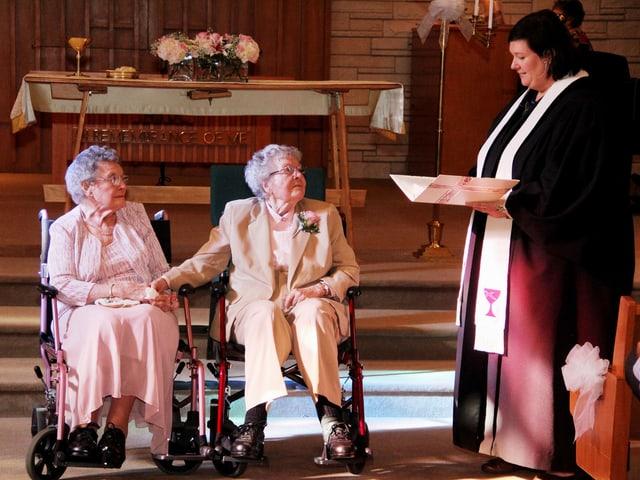 Zwei alte Frauen im Rollstuhl in einer Kirche