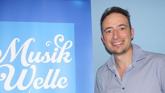 Bruno Zemp vor dem Musikwelle-Logo.