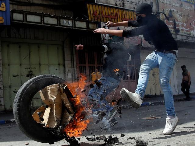 Junger Palästinenser stösst einen brennenden Reifen mit dem Fuss weg.