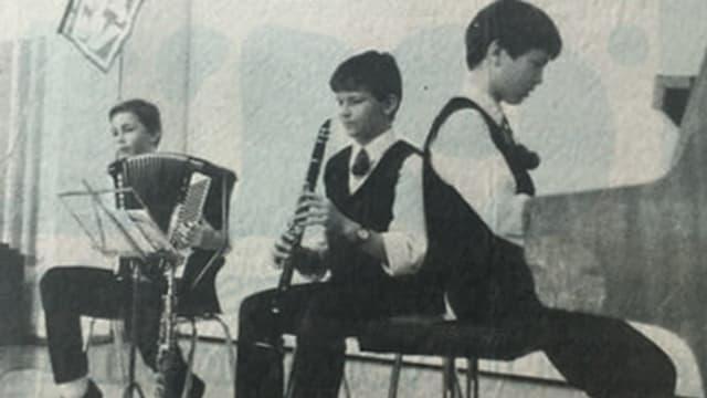 Schwarz-Weiss-Fotografie mit drei jungen Musikanten bei einem Auftritt.