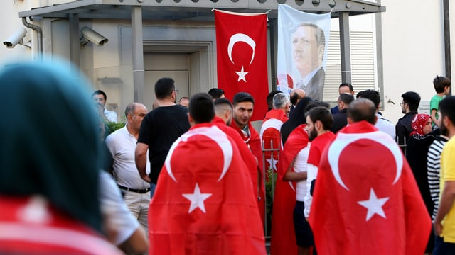 Mehrere Personen, von hinten fotografiert, viele haben eine türkische Fahnen über ihren Schultern.