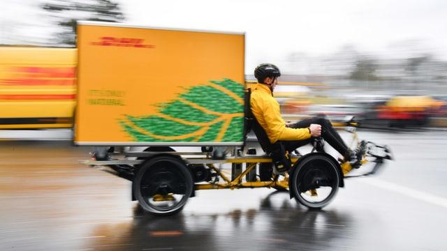 Ein DHL-Kurierfahrer ist mit einem Cargobike unterwegs.