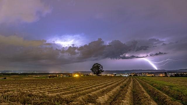 In der Ferne ist ein gewaltiger Blitzeinschlag zu sehen.