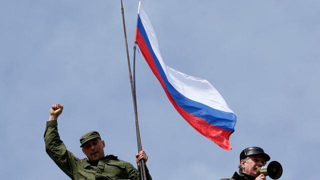 Soldaten hissen am 19. März 2014 an einem Marinestützpunkt in Sewastopol die russische Flagge.