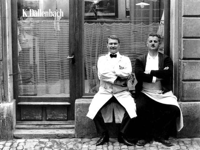 Zwei Männer sitzen vor einem Friseurgeschäft.
