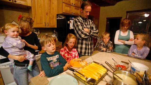 Eine Familie mit sechs Kindern steht um einen Tisch und betet.