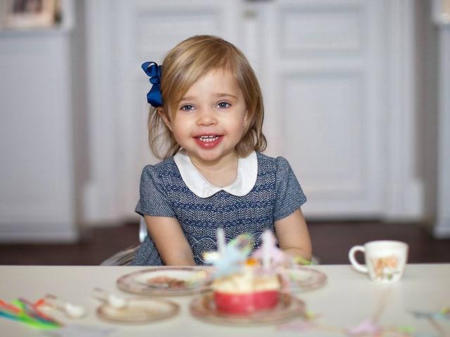 Ein Mädchen in blauem Kleidchen und blonden Haaren lächelt und blick in die Kamera. Sie sitzt an einem gedekten Tisch.
