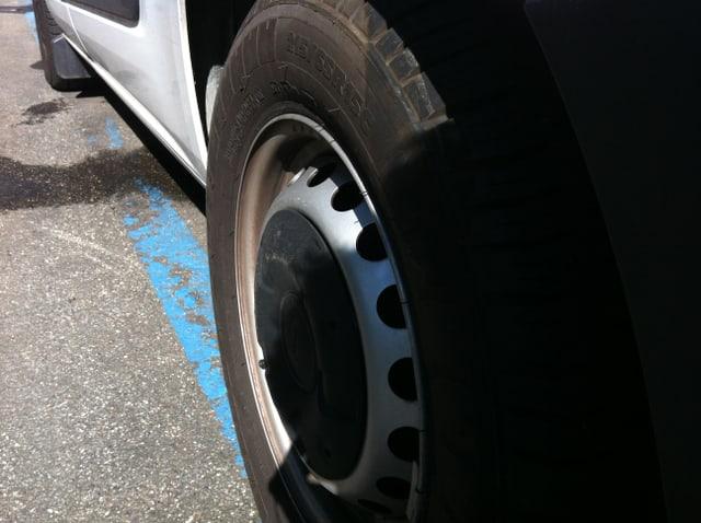 Auf dem Boden sieht man einen blauen Parkplatz angezeichnet, darauf steht ein Auto. Zu sehen sind das Hinterrad und ein Teil der blauen Markierung auf der Strasse.