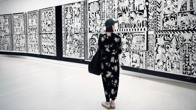 Frau in schwarz-weissem Klein steht vor schwarz-weissem Kunstwerk.