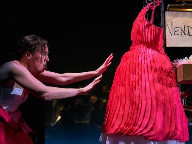 Frau mit ausgestreckten Armen Richtung rotes Kleid