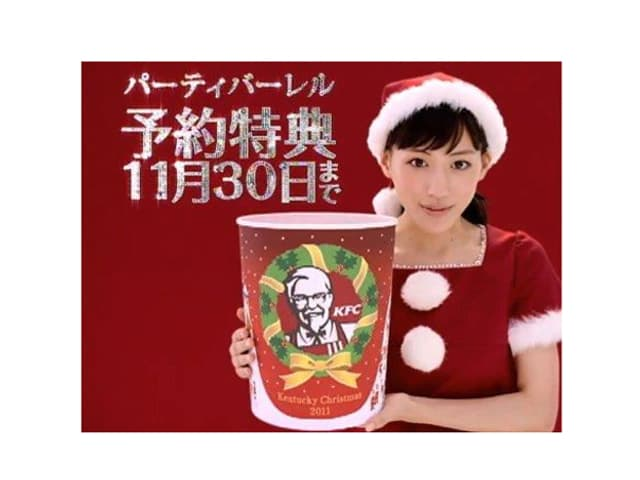 Eine Japanerin im Weihnachtsmann-Outfit hält einen Behälter der Fastfoodkette Kentucky Fried Chicken in die Kamera-