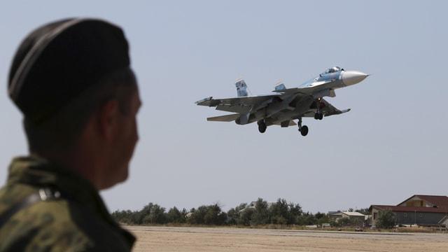 Ein Mann beobachtet einen fliegenden russischen Kampfjet.