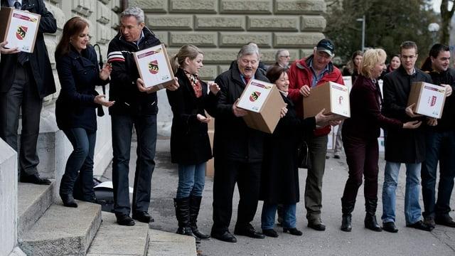 Menschen stehen in einer Reihe und geben sich Kartonkisten weiter.