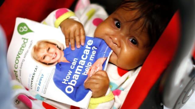 Ein Latino-Kleinkind im Wagen knabbert eine Broschüre zu «Obamacare» an.