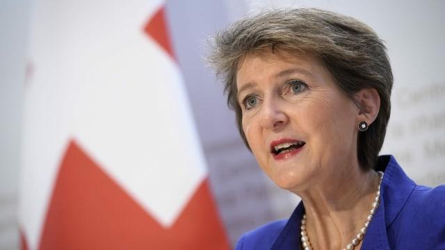 Bundespräsidentin Simonetta Sommaruga spricht an einer Medienkonferenz, im Hintergrund ist eine Schweizer Fahne zu sehen.