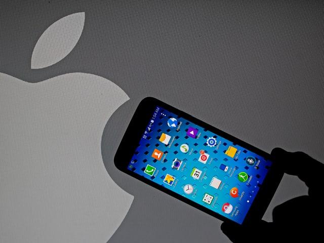 In telefonin da Samsung davant il logo alv da Apple.