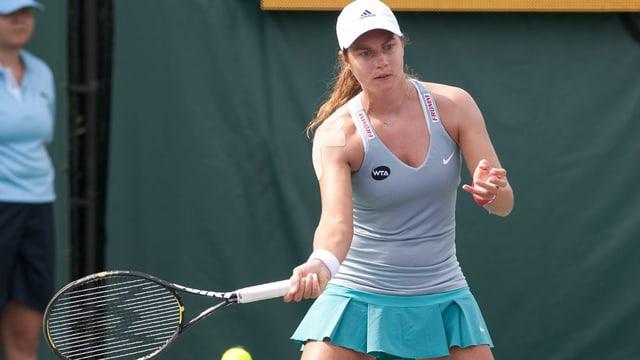 Tennisspielerin schlägt Ball