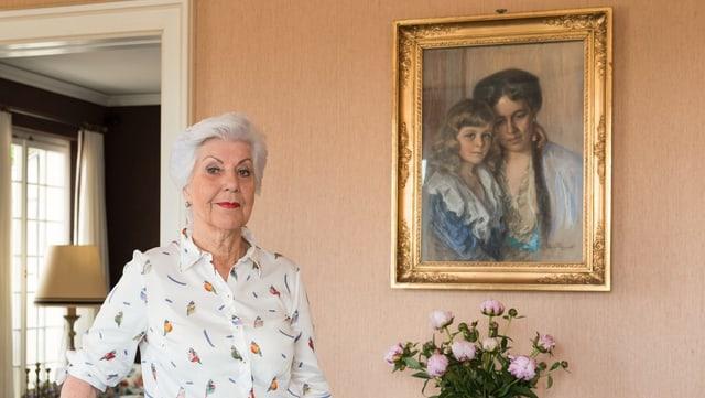 Eine Frau vor dem Gemälde einer Mutter und ihres Sohnes.