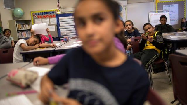 Symbolbild: Aufnahme eines Klassenzimmers mit herumlümmelnden Schülern.