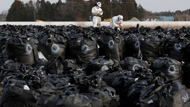 Hunderte schwarze Säcke mit kontaminierter Erde, im Hintergrund zwei Personen in weissen Schutzanzügen.