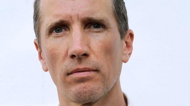 Ein Mann mit kurzem Haar und ernstem Blick.