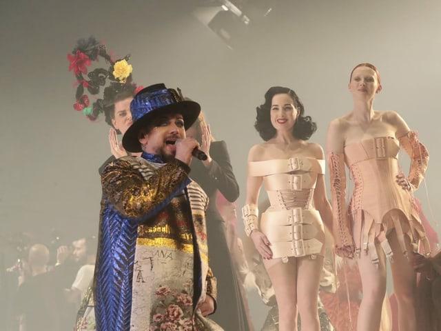 Boy George singt, daneben laufen Dita von Teese und ein Model.
