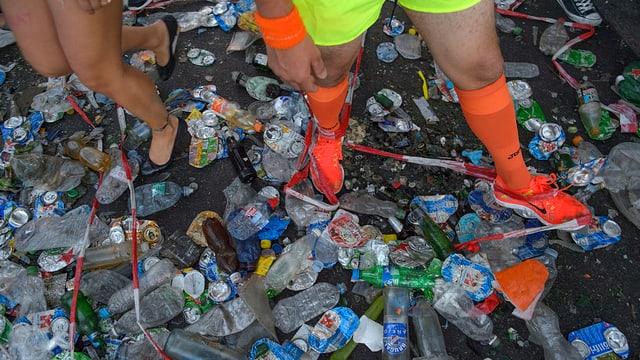 Plastikbecher, Dosen und Petflaschen am Boden.