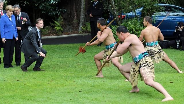 Angela Merkel beobachtet eine Maori Tanzzeremonie.