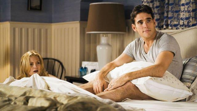 Zwei Schauspieler liegen auf und am Bett.