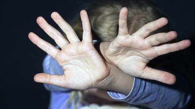 Symbolbild: Ein Kind hält die Hände abwehrend vor den Kopf.