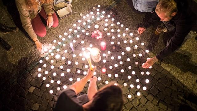 Menschen zünden herzförmigen Kerzen an einer Mahnwache in Zürich