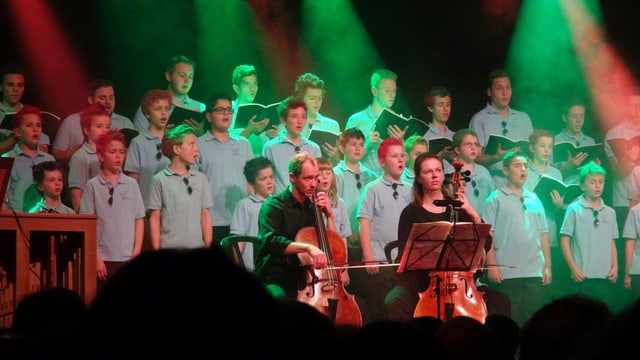 Chor-Mitglieder tragen blaue Polo-Hemden, Haare in verschiedenen Farben gefärbt. Im Vordergrund zwei Cellisten.