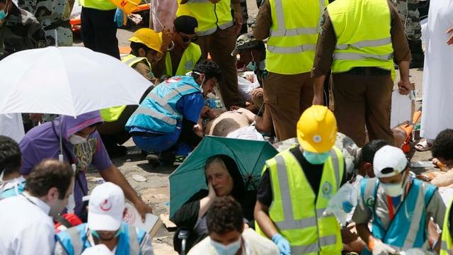 Personen in Leuchtwesten und Verletzte am Boden.